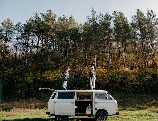 Homme et femme debout sur une camionnette à l'extérieur