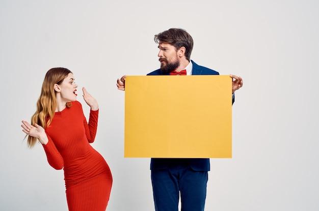 Homme et femme debout côte à côte maquette jaune publicité fond clair espace copie