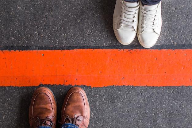 Homme et femme debout l'un en face de l'autre de chaque côté de la route, séparés par une ligne rouge.
