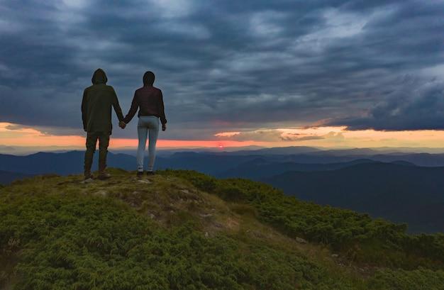 L'homme et la femme debout sur le magnifique fond de coucher de soleil