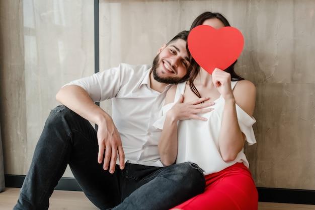Homme et femme derrière la carte de saint valentin en forme de coeur rouge assis à la maison sur le sol