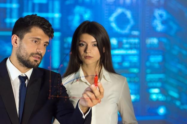 L'homme et la femme dessinant sur le fond d'écran virtuel