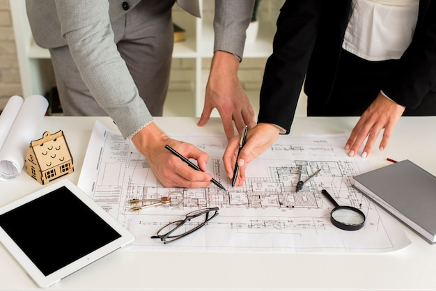Homme et femme dessinant un plan de maison