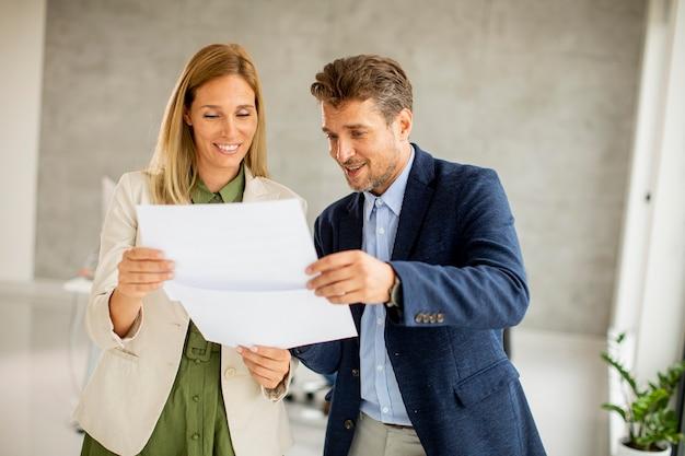 Homme et femme discutant avec du papier dans les mains à l'intérieur dans le bureau avec des jeunes travaille derrière eux