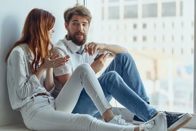 Homme et femme discutant près de la fenêtre ensemble technologie des appartements