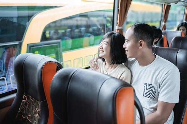 Un homme et une femme discutant et regardant par la fenêtre alors qu'il était assis dans le bus lors d'un voyage