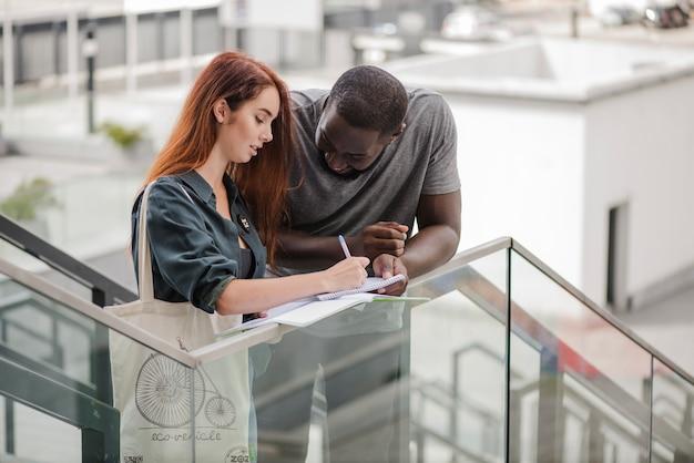 Homme et femme avec des documents sur les escaliers