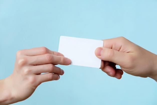 Homme et femme donnant des mains de carte en plastique bouchent isolé, espace copie