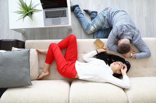 L'homme et la femme dorment à côté d'une bouteille d'alcool