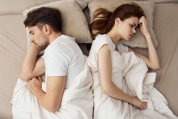 Homme et femme dorment dans son lit, téléphone, tricherie, relation amoureuse