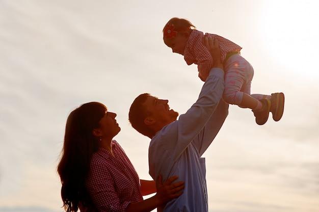 Homme et femme élèvent l'enfant dans les bras