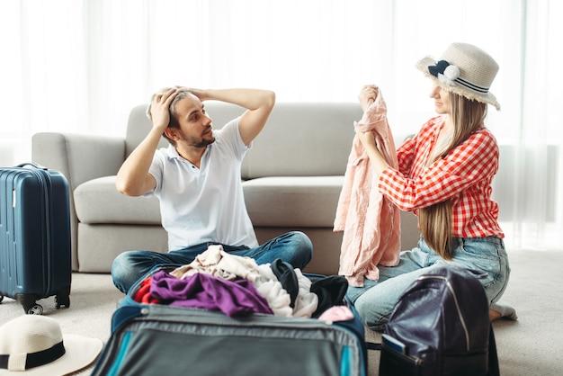 Homme et femme emballant leurs valises pour les vacances
