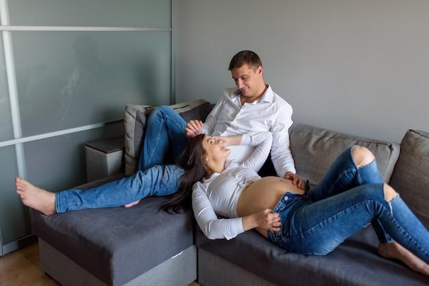 Homme et une femme enceinte. futurs parents à la maison. femme gisait sur le pied de son mari.