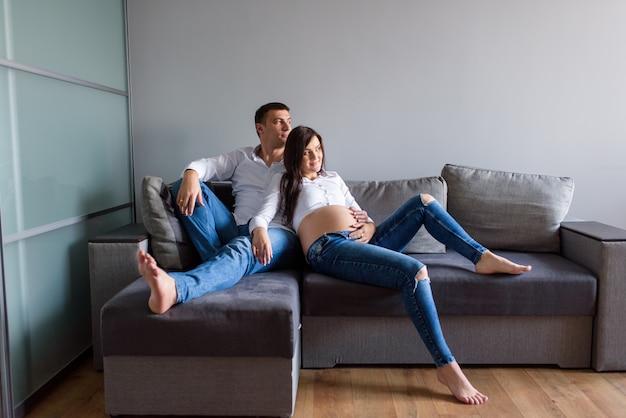 Homme et une femme enceinte sont assis étreignant sur le canapé.