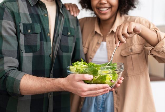 Homme et femme essayant une salade savoureuse