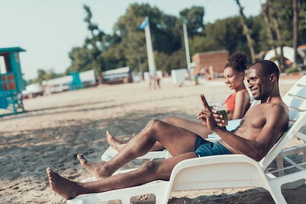Homme et femme est allongé sur des chaises longues et boit des cocktails