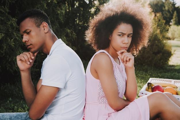 Homme et femme est assis dos à dos et pense