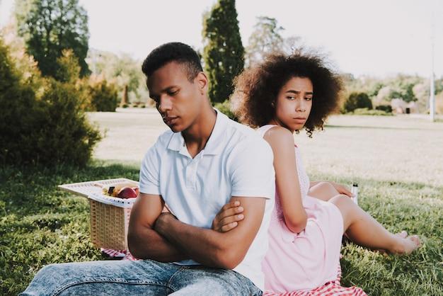 Homme et femme est assis dos à dos et silencieux