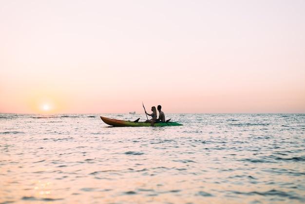 Homme et femme explorant l'océan dans un kayak