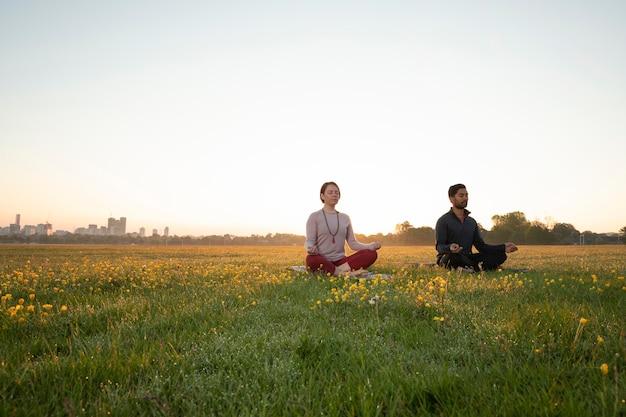 Homme et femme faisant du yoga ensemble à l'extérieur