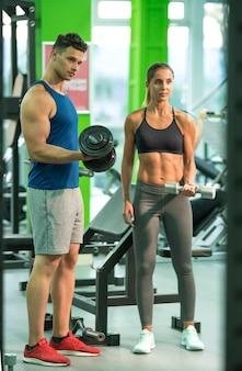 L'homme et la femme faisant de l'exercice avec un haltère dans le centre de remise en forme