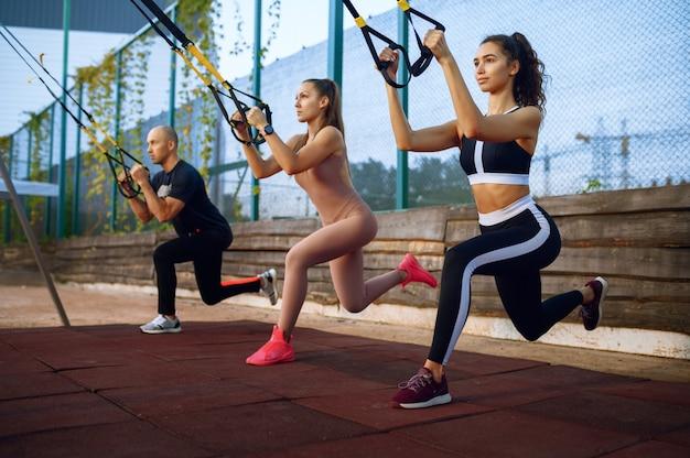 Homme et femme faisant de l'exercice sur un terrain de sport en plein air, entraînement de fitness en groupe