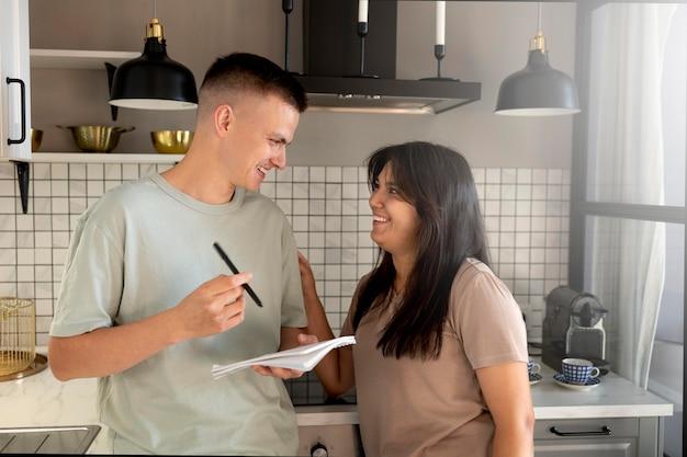 Homme et femme faisant une liste de courses à la maison dans la cuisine ensemble