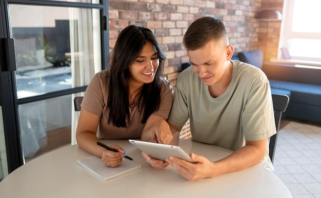 Homme et femme faisant une liste de courses avec tablette