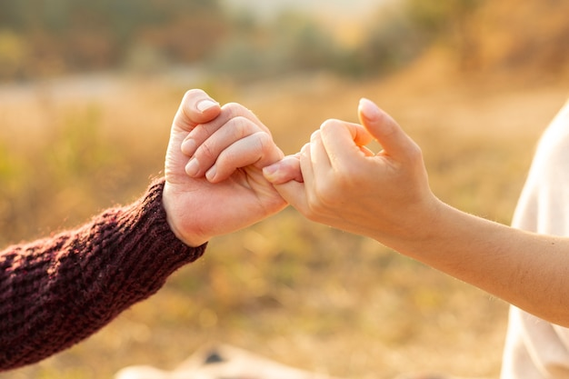 Homme et femme faisant une promesse de petit doigt