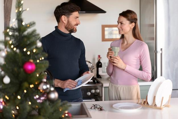 Homme et femme faisant la vaisselle ensemble à noël