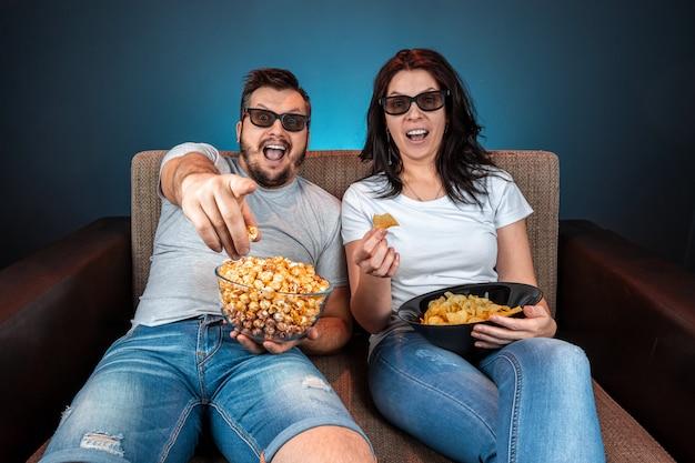 Un homme et une femme, une famille regardant un film ou une série de lunettes 3d, un mur bleu. le concept de cinéma, films, émotions, surprise, loisirs, plateformes de streaming.