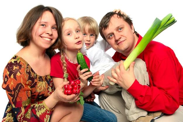 Homme, femme, fille et garçon tenant des légumes