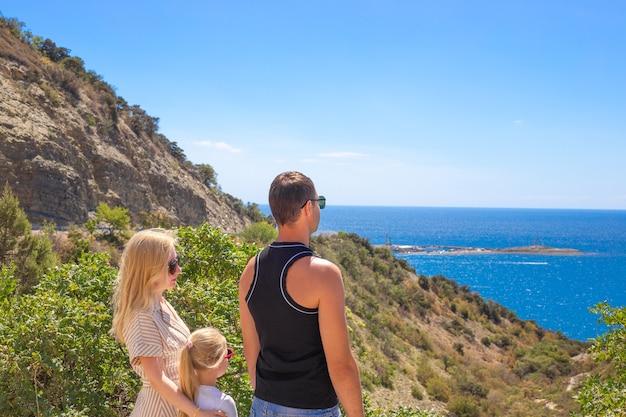Un homme, une femme et une fille sur le pont d'observation regardent la mer et les montagnes. concept de voyage et de tourisme. vacances d'été en famille.
