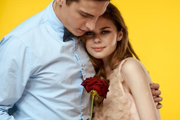 Homme et femme avec fleur rouge sur fond jaune modèle de noeud papillon vue recadrée.