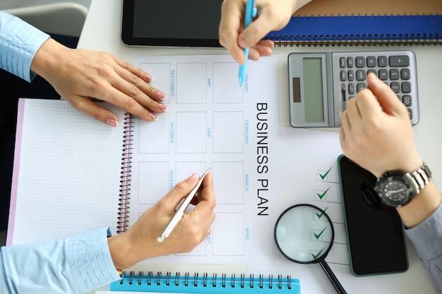 L'homme et la femme font un plan d'affaires sur papier