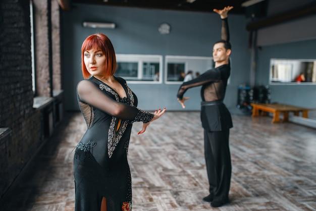 Homme et femme sur la formation de danse ballrom en classe. partenaires féminins et masculins sur un couple professionnel dansant en studio