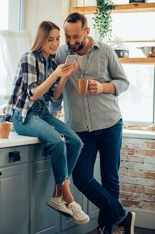 Homme et femme gais dans la cuisine souriant et regardant le smartphone