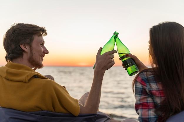 Homme et femme grillage avec des bouteilles de bière au coucher du soleil