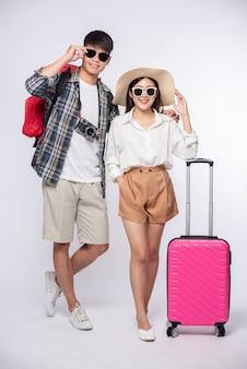 Homme et femme habillés en portant des lunettes pour voyager avec des valises