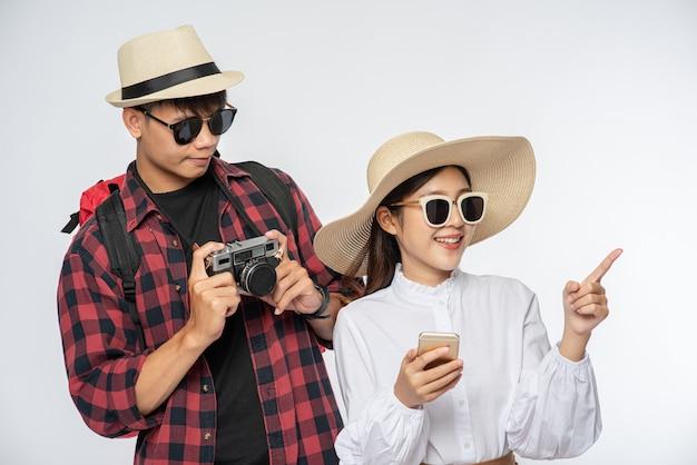 Homme et femme habillés pour voyager, porter des lunettes et prendre des photos