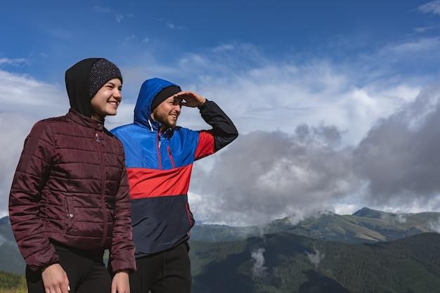 L'homme et la femme heureux debout sur une montagne avec une belle vue