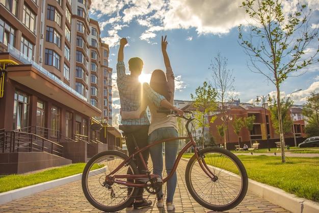 L'homme et la femme heureux se tiennent avec un vélo et font un geste près d'un bâtiment