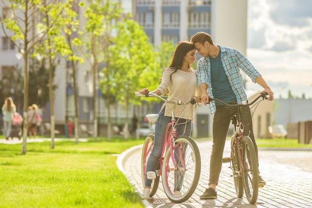 L'homme et la femme heureux se tiennent avec des vélos dans un complexe résidentiel