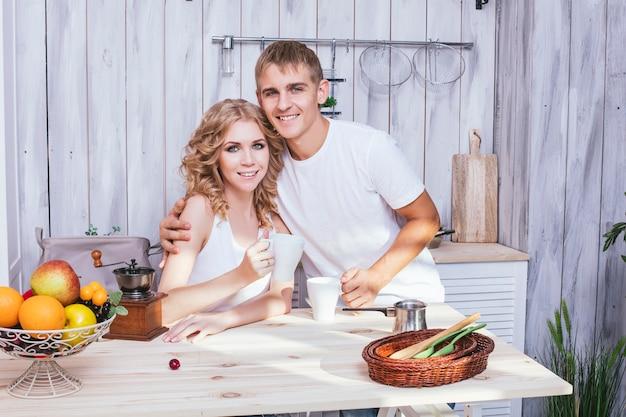 Homme et femme jeune et beau couple dans la cuisine maison cuisiner et prendre le petit déjeuner ensemble, s'entraider