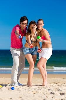 Homme et femme jouant à la boule sur la plage