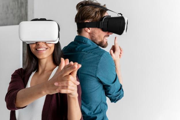 Homme et femme jouent ensemble avec un casque de réalité virtuelle à la maison