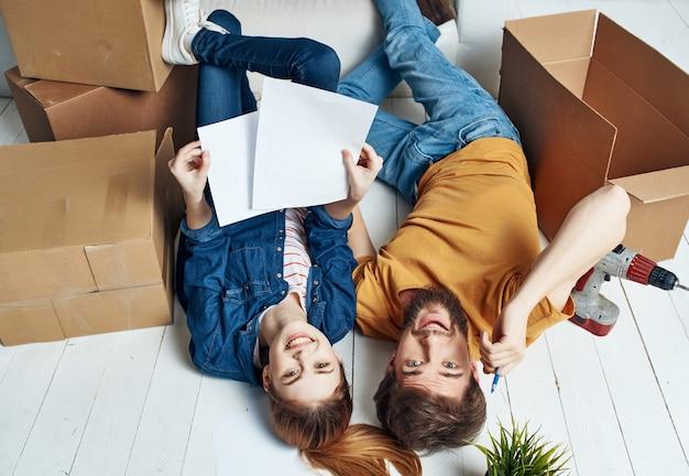Un homme et une femme joyeux sont allongés sur le sol dans une pièce avec des boîtes en mouvement