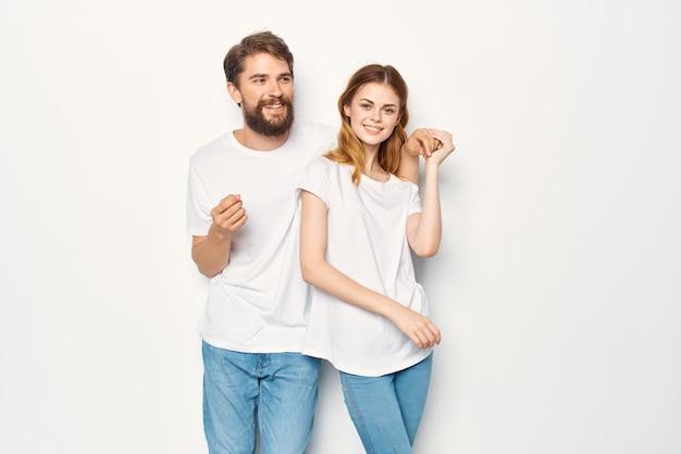 Un homme et une femme joyeux en t-shirts blancs embrassent l'amitié ensemble