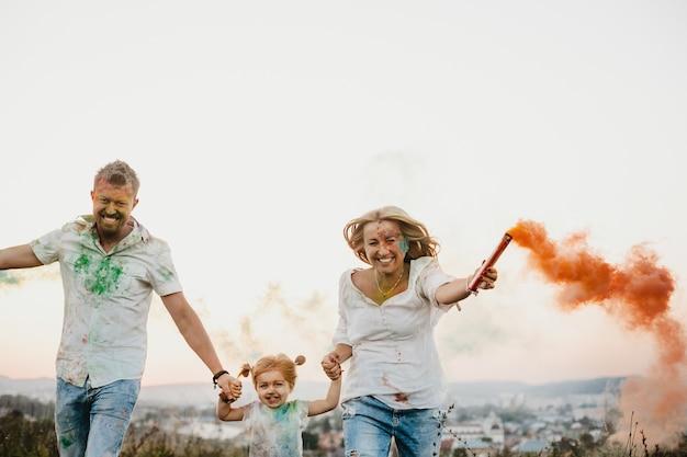 Homme, femme et leur petite fille s'amusent à courir avec de la fumée colorée dans les bras