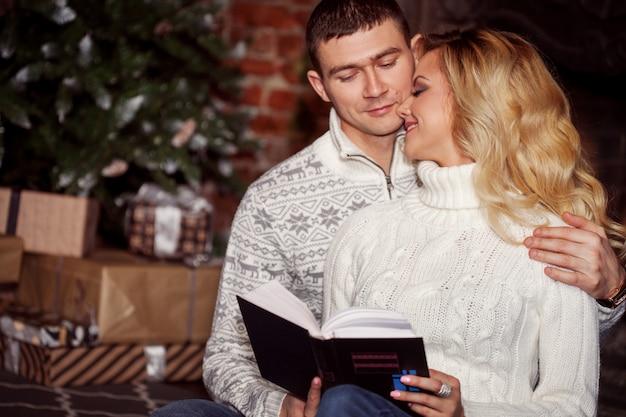 Homme et femme lisant un livre ensemble sur le sapin de noël